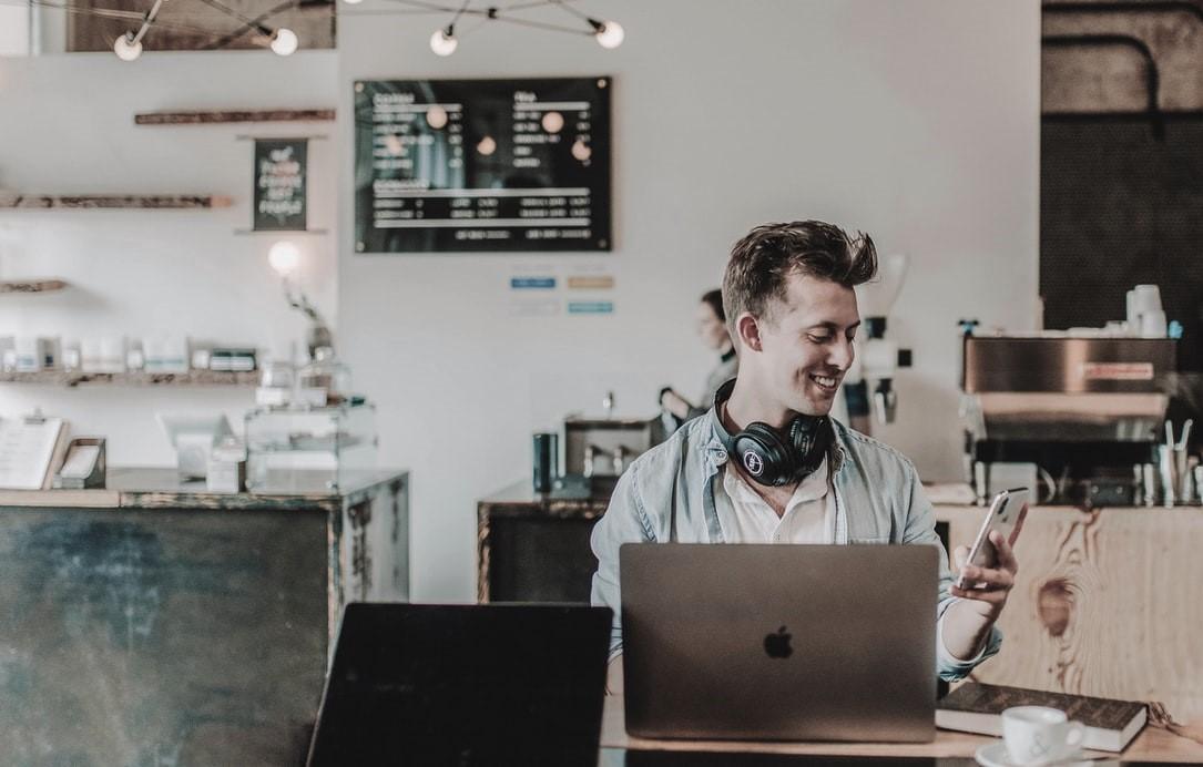 arbeitender_Mann_laptop_Iphone_Kopfhörer_Café_Restaurant_mobiles_arbeiten